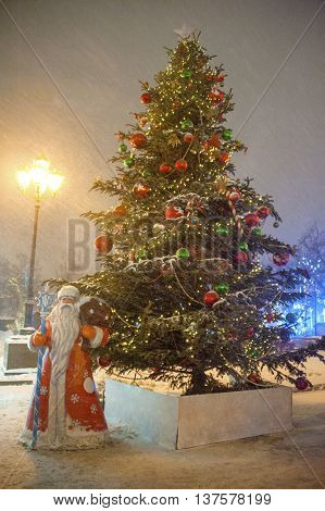 christmas tree with figure of santa claus on winter snowy city street at night
