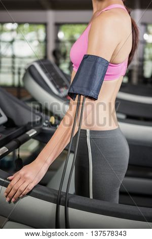 Mid section of woman at gym exercising on treadmill with mobile on armband