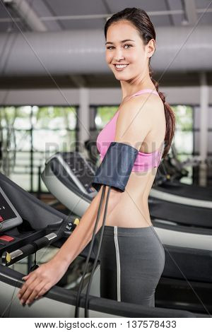 Portrait of woman at gym exercising on treadmill with mobile on armband