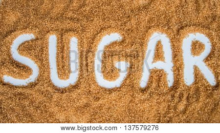 The word sugar written over a pile of brown sugar