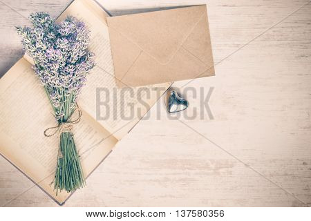Lavender bouquet laid over an old book a silver heart and a kraft paper envelope on a white wooden background. Vintage style.