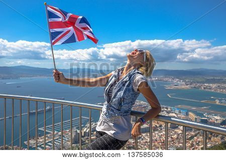 Happy woman waving a British flag on top of Gibraltar Rock.