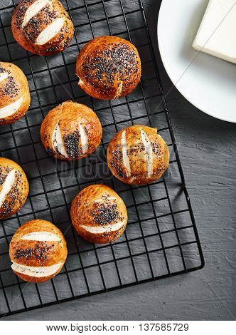 Top view of group homemade baked golden pretzel buns with poppy seeds on stone background. Pretzel bun is german cuisine dish, ideal for lunch or breakfest with butter and tea.