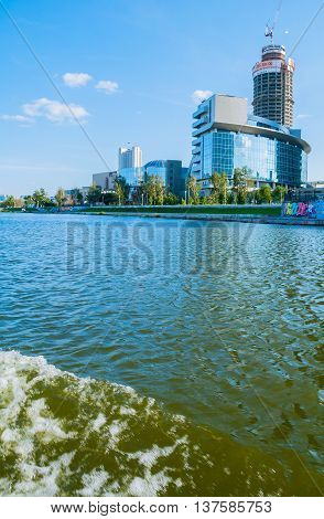 YEKATERINBURG RUSSIA -AUGUST 24 2013. Urban summer architecture view- modern business and administrative skyscraper buildings on the embankment of Iset river with splashing water on the foreground