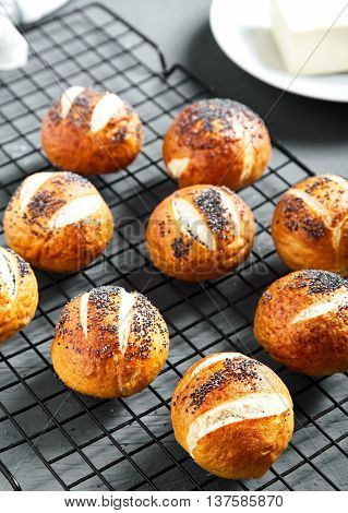 Group of homemade baked golden pretzel buns with poppy seeds on stone background. Pretzel bun is german cuisine dish, ideal for lunch or breakfest with butter and tea.
