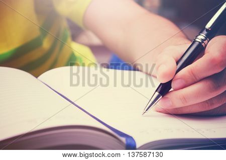 Write activity (A girl hand holds a pen and write on a book) filtered with morning light