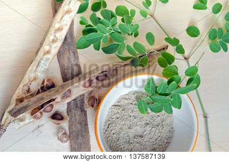 Moringa Grinded Leaf And Seed On Wooden Board Background