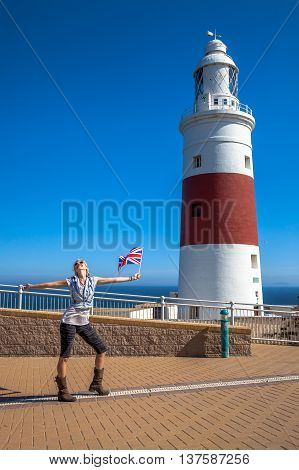 Happy young tourist woman waving a British flag. Europa Point Lighthouse on the southernmost point of Gibraltar where you can see the Strait and Africa.