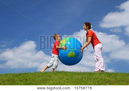 Mother with  son play an inflatable globe in  day-time stand  on  grass