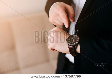 businessman in black suit look at his expensive swiss wristwatch on his hand and watching the time.