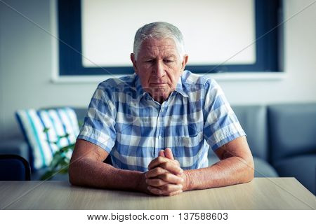 Worried senior man sitting in living room at home