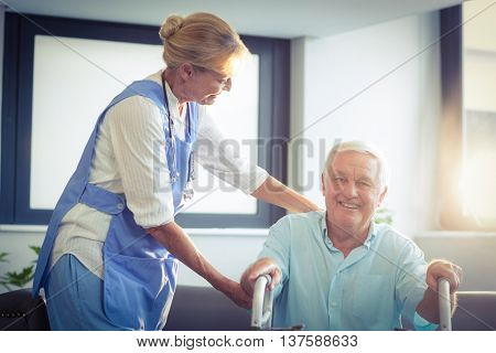 Female doctor helping senior man to walk with walker at home