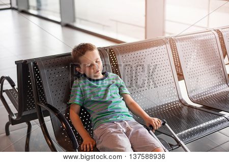 Tired Child Sleeping In Waiting Room For Passengers.