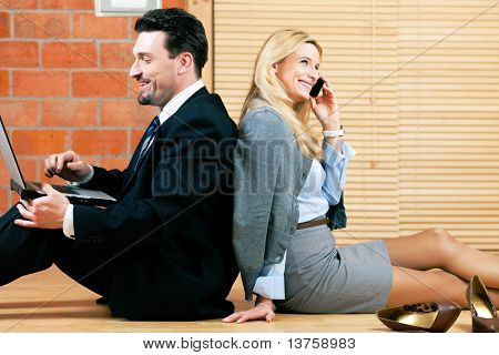 Couple � businesswoman and businessman � working at home sitting on the floor