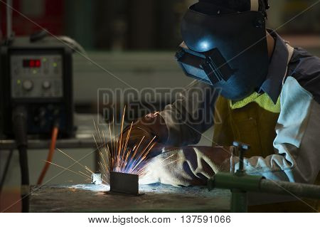 man welding steel by skill.Men wear protective clothing during work.