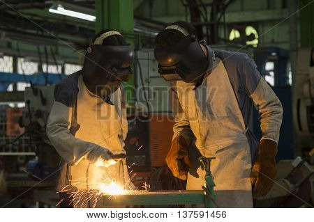 workers with protective mask welding metal in factory