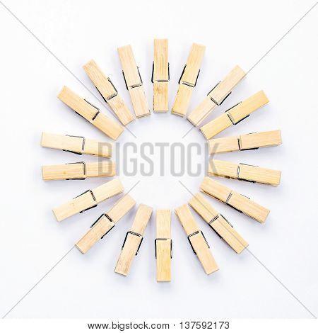 Group of wooden clothespins arranged in a circle isolated on white background.