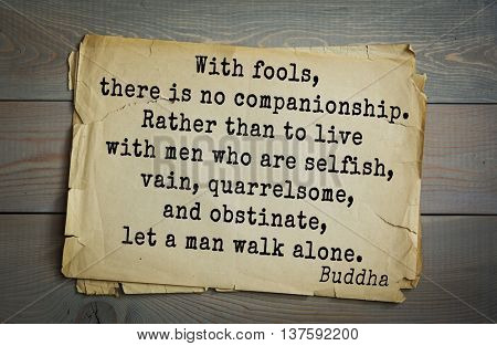 Buddha quote on old paper background. With fools, there is no companionship. Rather than to live with men who are selfish, vain, quarrelsome, and obstinate, let a man walk alone.