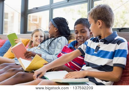 School kids sitting on sofa and reading book in library at school