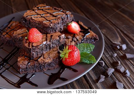 Chocolate brownies with strawberries on a wooden background