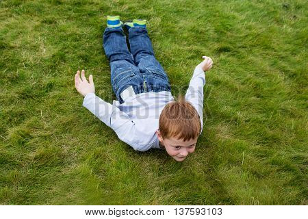 Little boy laying on the grass in sliding pose playing in the yard
