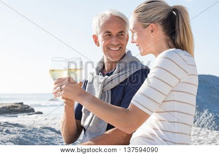 Happy romantic mature couple enjoying glass of white wine on the beach. Cheerful senior couple raising a toast celebrating wedding anniversary.