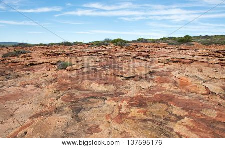 Rugged sandstone landscape under a blue sky at the Red Bluff  hiking location in Kalbarri, Western Australia