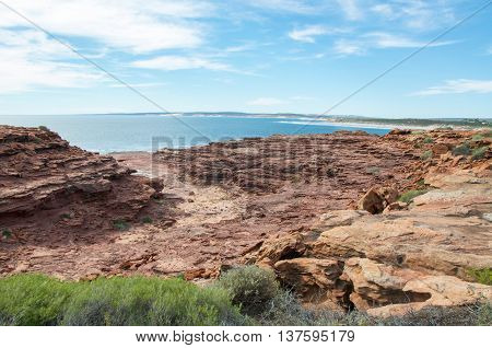 Elevated view over the coastal red sandstone at Red Bluff beach with the turquoise Indian Ocean seascape on the coral coast in Kalbarri, Western Australia.