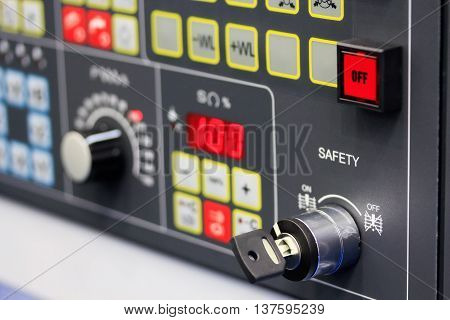 Control panel of modern industrial equipment. Close up view. Selective focus on SAFETY key switch.