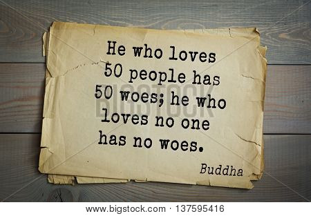 Buddha quote on old paper background. He who loves 50 people has 50 woes; he who loves no one has no woes.