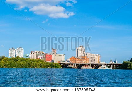 YEKATERINBURG RUSSIA - AUGUST 24 2013.Panoramic view of modern and historic buildings along the embankment and Makarov bridge- the longest bridge across the Iset river in Yekaterinburg Russia