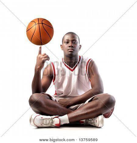 Joven africana sostiene una pelota de baloncesto en su dedo