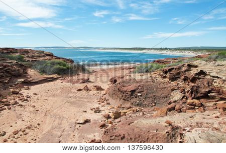 Rugged sandstone path with coastal plants to the Red Bluff beach with the stunning turquoise Indian Ocean waters on the coral coast in Kalbarri, Western Australia.