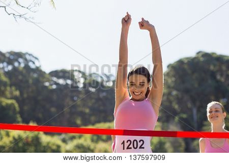 Cheerful winner female athlete crossing finish line with arms raised in park