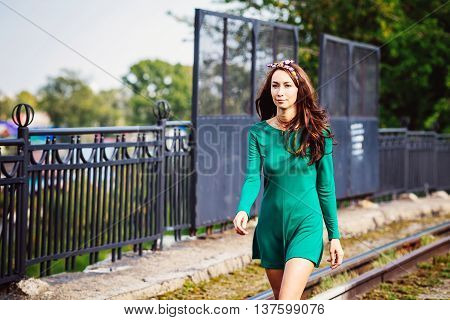Girl walking along the road in the city, Sunny summer day, developing green dress