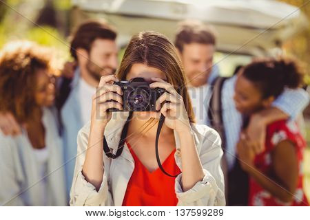 Woman clicking a photo from camera in park on sunny day