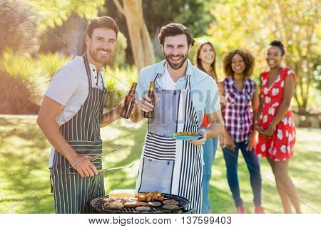 Two men holding a beer bottle while preparing barbecue grill in park and friends in background