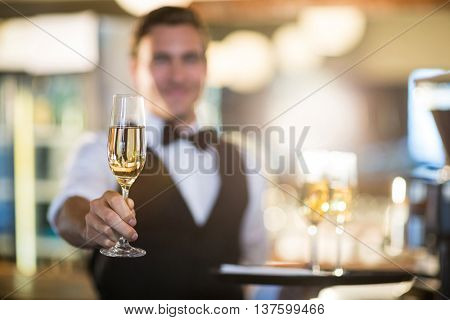 Waiter offering a glass of champagne in restaurant