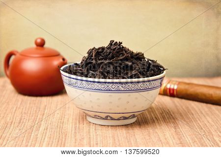 Chinese tea leaves and ceramic pot over retro background
