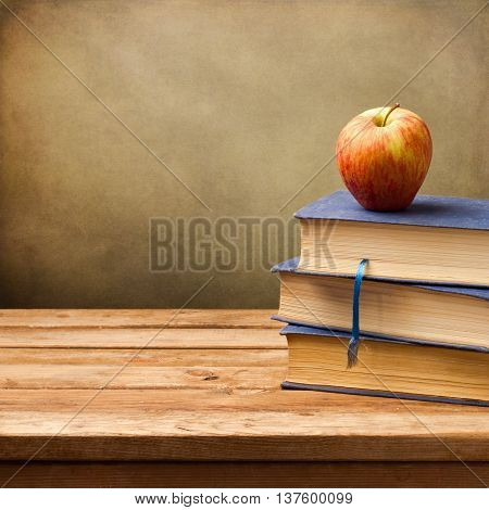 Background with vintage books and apple over wooden table