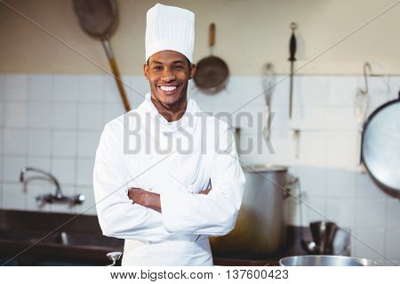 Portrait of happy chef standing with arms crossed in commercial kitchen