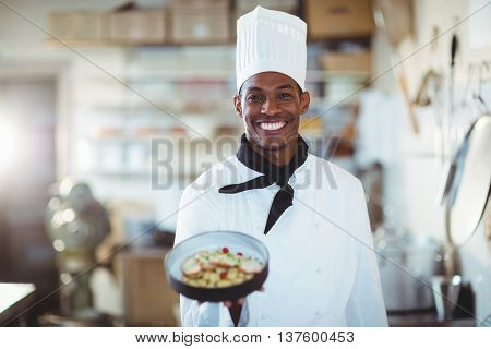 Portrait of head chef presenting salad in commercial kitchen