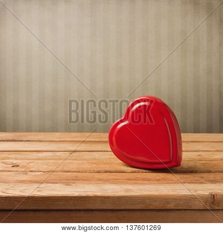 Heart shape box on wooden table over striped wall