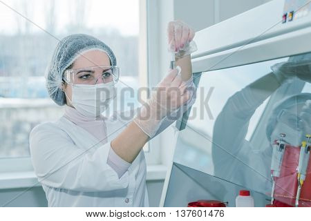 Woman scientist in a white protective clothing conducts research in a real lab