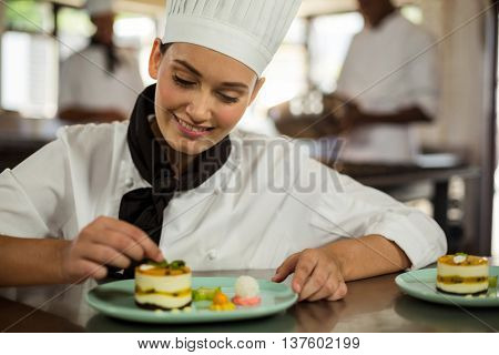 Female chef finishing dessert plates in commercial kitchen