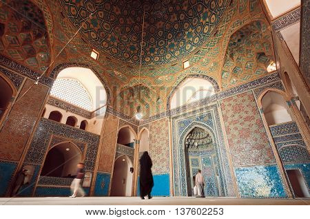 YAZD, IRAN - OCT 19, 2014: Old Persian mosque and people praying inside of tiled hall on October 19, 2014. With population of 270.600 families Yazd is centre of Persian architecture