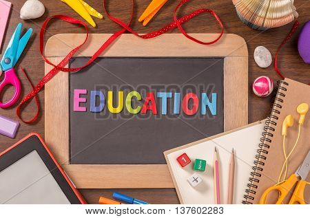 Education word formed by color wooden alphabets on small blackboard with school supplies on wooden table
