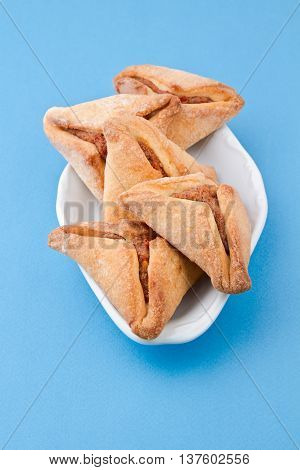 Hamantaschen cookies forJewish festival of Purim on blue background