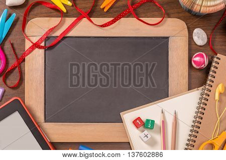Small blackboard with school supplies on wooden table empty space on small blackboard for text or other graphics