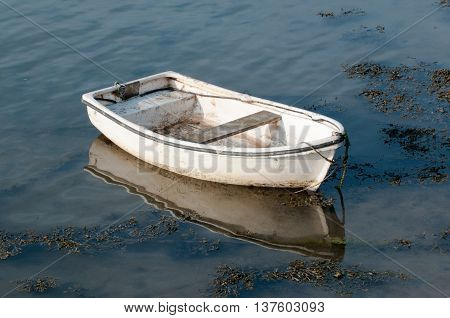 Small fishing boat at sunrise moored in the water ready for sailing